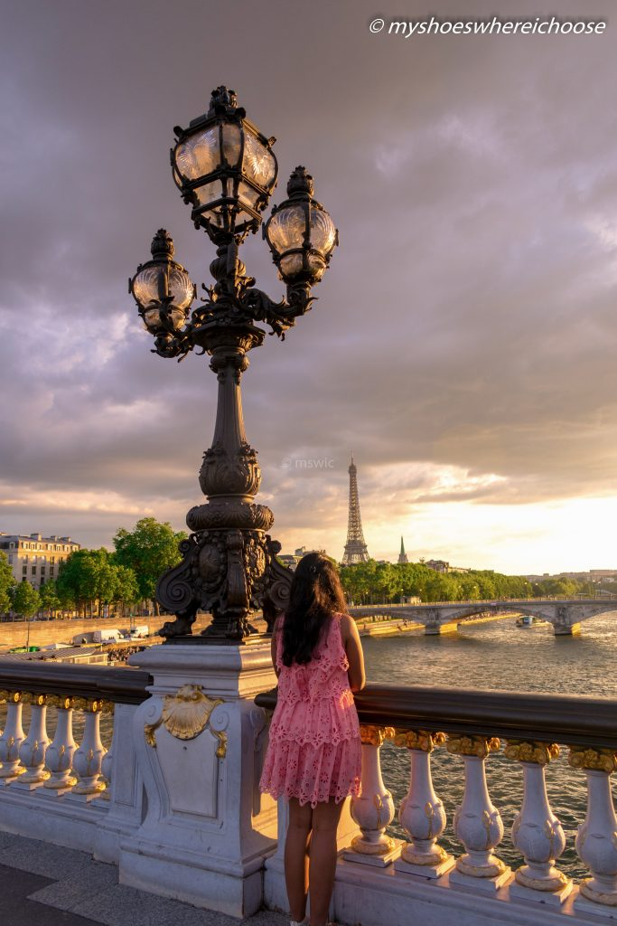 Looking at a dreamy sunset and dramatic sky from Pont Alexander III with the Eiffel Tower in view in Paris.