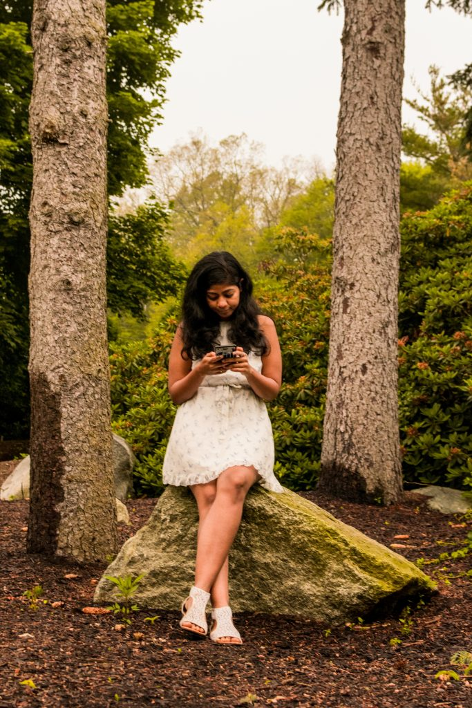 Girl surrounded by beautiful nature, but lost in their phone.