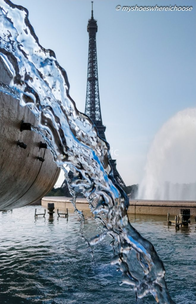 View of Eiffel Tower at Paris from Trocadero trough the perspective of the fountains.