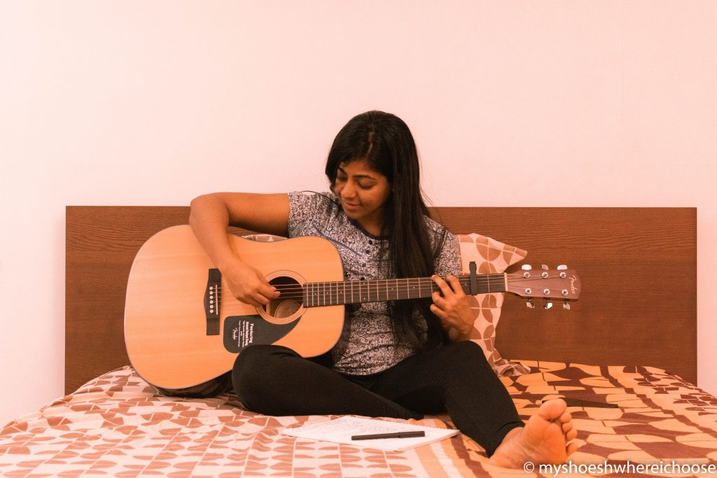 Girl sitting on bed and enjoying a guitar session.