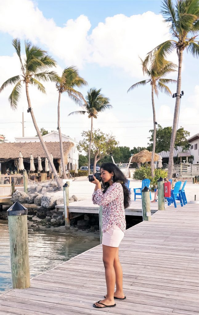 Girl with camera with palm trees