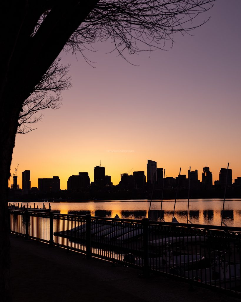 Boston skyline silhouette at sunrise as seen from Cambridge